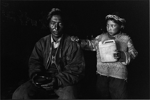 TIBET. 2001. Daughter pouring liquor for her fathe